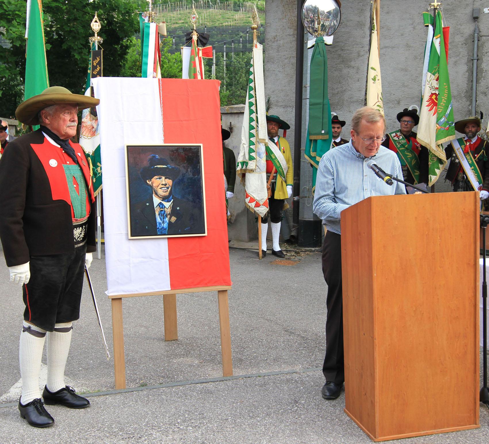 Roland Lang bei seiner Ansprache und das Portrait von Luis Amplatz. (Bild: Südtiroler Schützenbund)